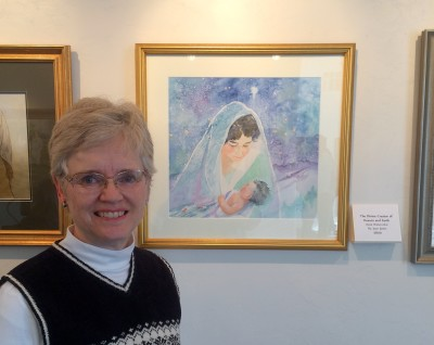 Joan Justis artist standing next to her painting